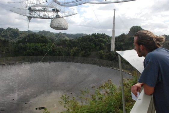 Four thousand square feet of aluminum paneling make up the Arecibo radio satellite dish, the sensitive receiver in the world.